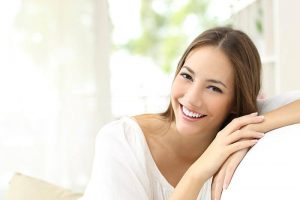 woman smiling while leaning on couch