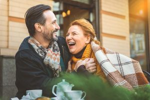 middle-aged couple laughing and leaning into each other at an outdoor cafe