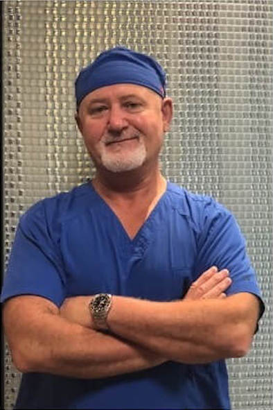 dentist wearing blue scrubs and cap with arms crossed