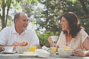 middle-aged couple smiling while sharing a meal