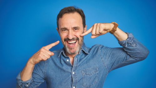 Man pointing at his smile with both hands