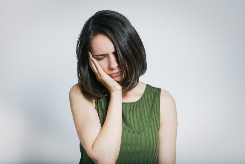 Woman has a toothache isolated on a gray background